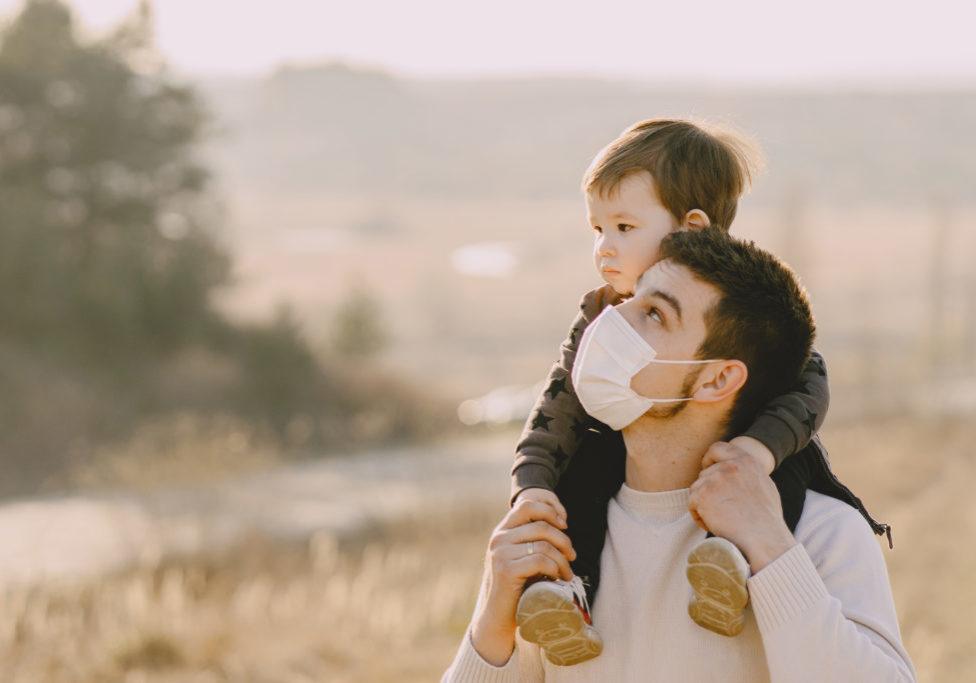 Family in a autumn field. Father in a white sweater. Cute little son. Coronavirus theme.